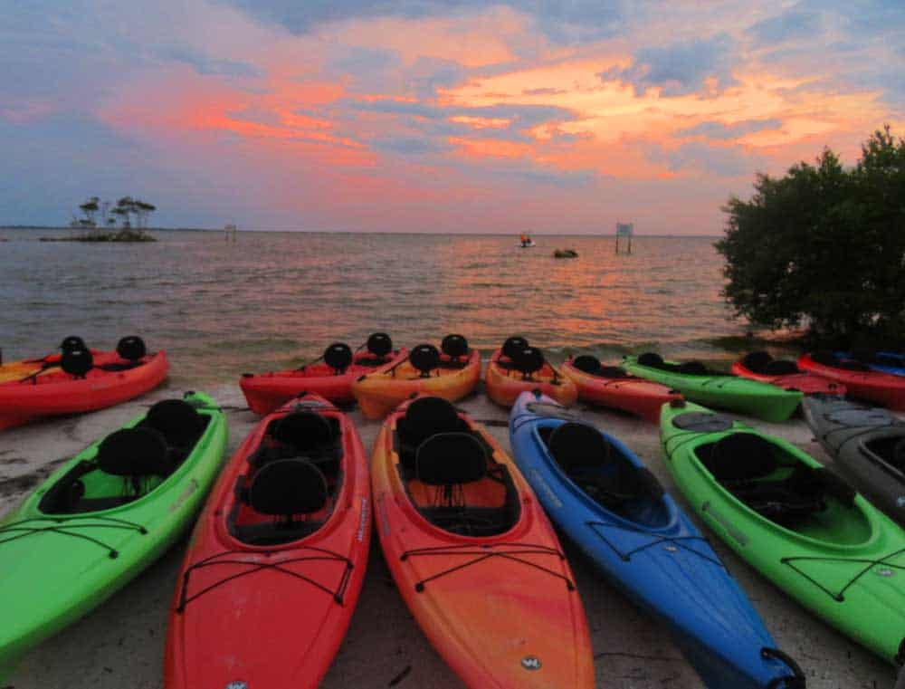 As the sun sets over Merritt Island National Wildlife Refuge, kayaks are lined up ready to launch for a bioluminescence kayaking trip. (Photo: Bonnie Gross)