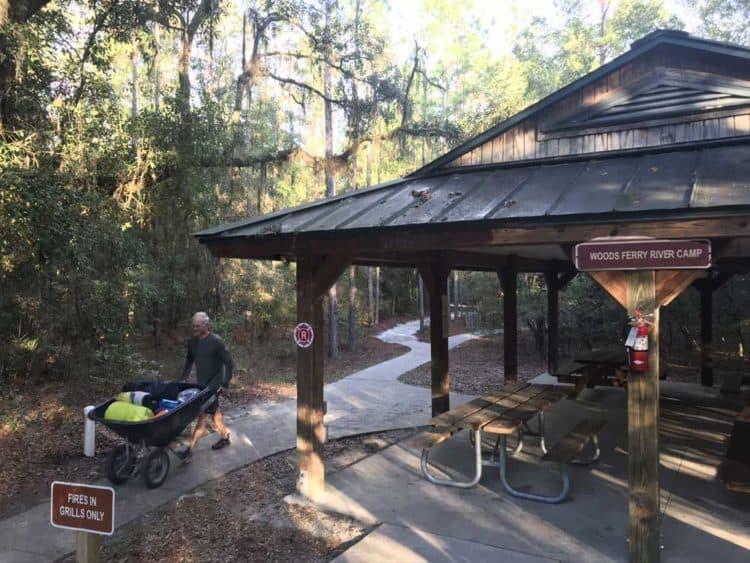 Man with wheelbarrow and pavilion
