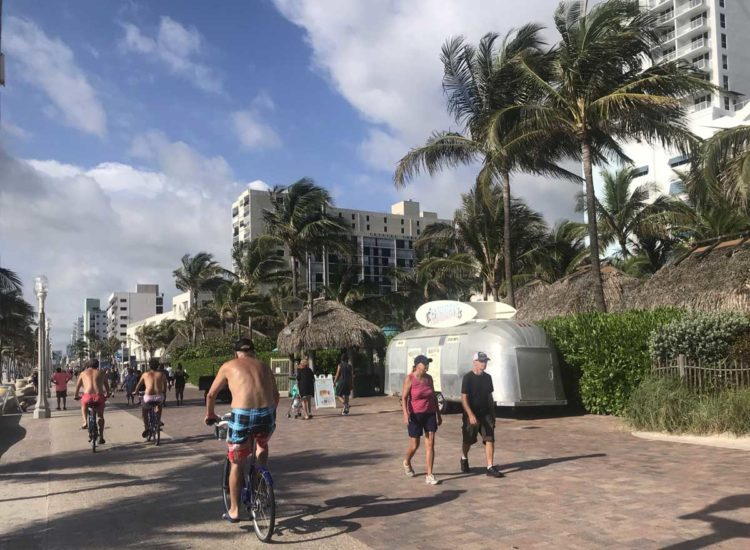 Bicyclists along the Hollywood Beach Broadwalk pass the Jimmy Buffett Margaritaville Resort, with its vintage RV, which sells snacks, beverages and sandwiches. (Photo: Bonnie Gross)